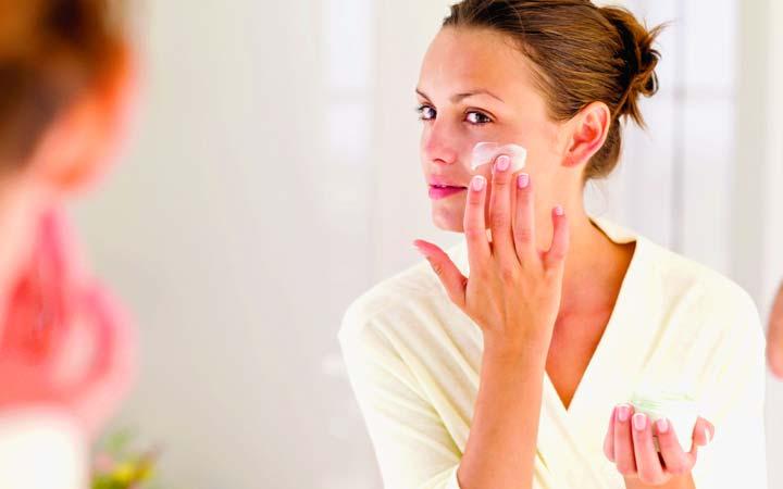 Нанесение крема на лицо перед процедурой парафинотерапии